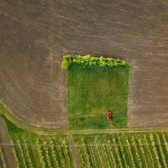 O velho carro vermelho fica em um trecho de estrada verde perto do campo tratado, pronto para o plantio. a vista superior é filmada por drones. fundo de natureza com carro.