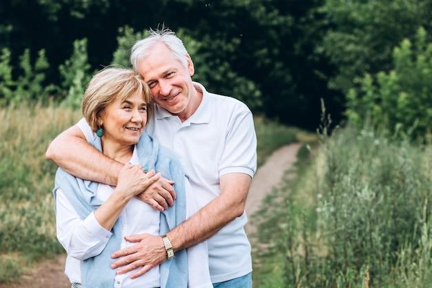 O velho casal caminha na natureza, dá as mãos, abraça