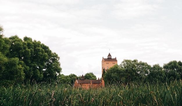 O velho castelo coberto de plantas de escalada sobe na margem do lago