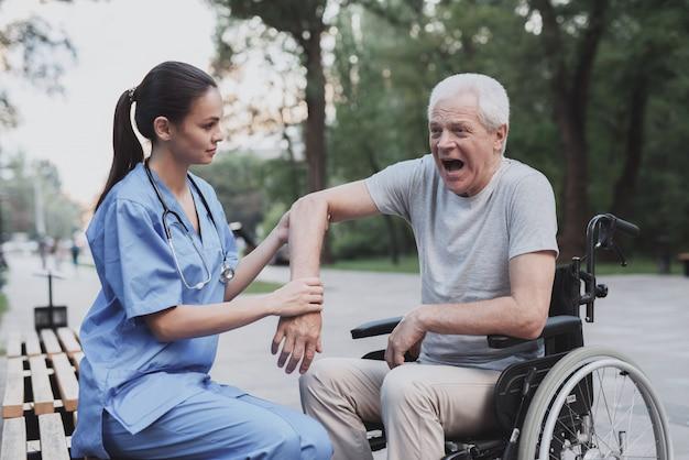 O velho deu a enfermeira para examinar seu cotovelo que dói