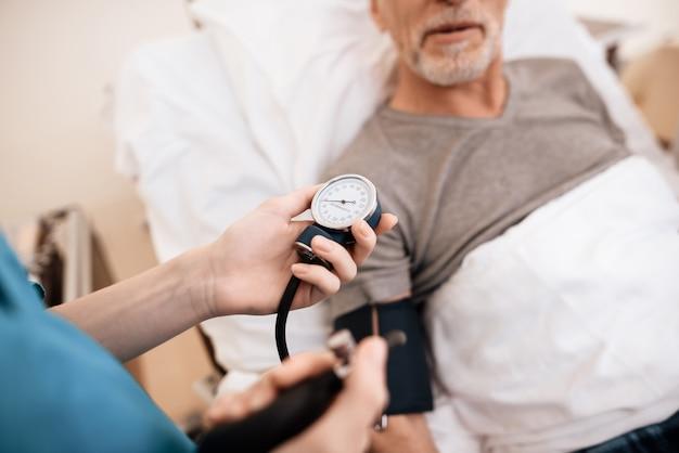 O velho encontra-se em uma cama na enfermaria, a enfermeira mede a pressão.