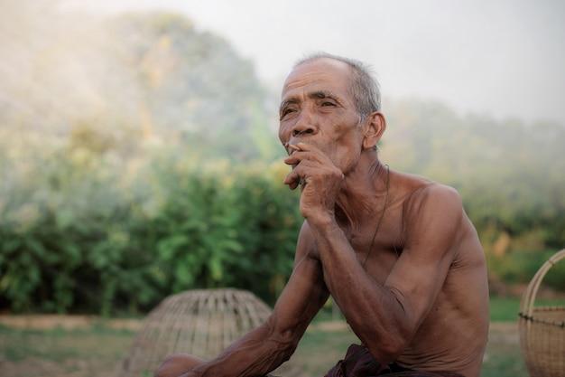O velho está fumando no campo da tailândia.