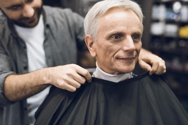 O velho está sentado na cadeira do barbeiro