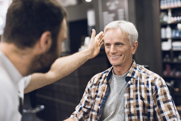 O velho está sentado na cadeira do barbeiro.