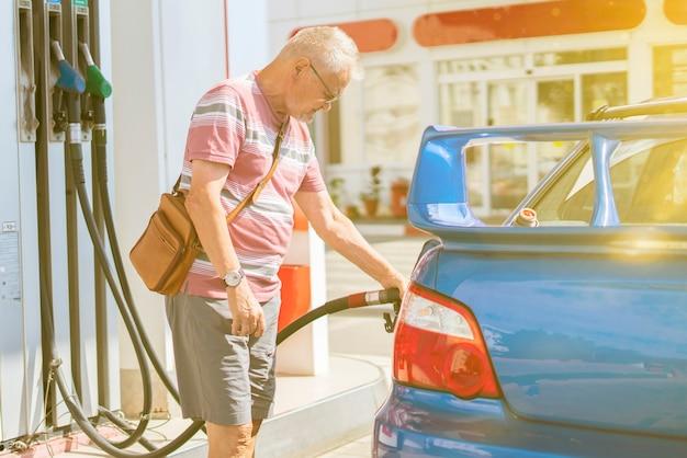 O velho homem reabastece seu carro com gasolina no posto de gasolina turista viajando