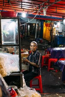 O velho muçulmano que vende mie goreng no mercado noturno.