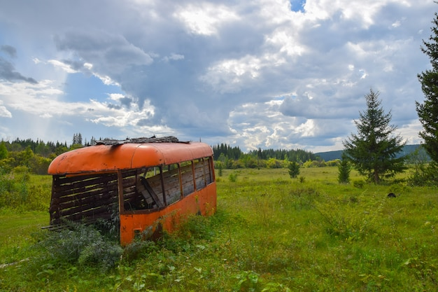 O velho ônibus em um campo. verão de 2016, oblast de irkutsk, na rússia.