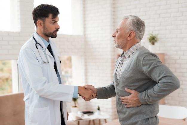 O velho se queixa de médico sobre a dor no baço.