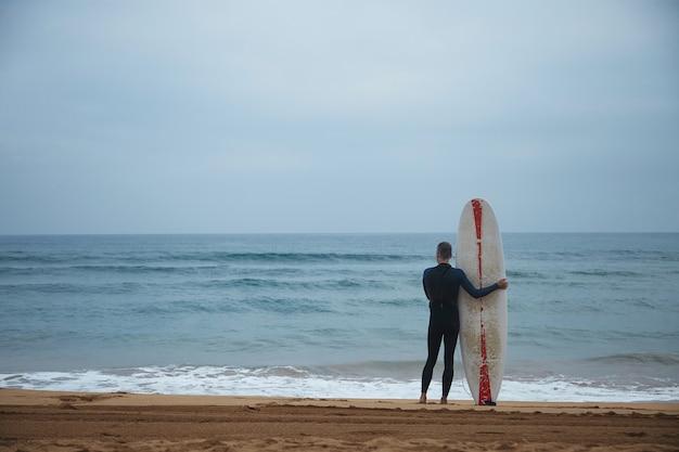 O velho surfista com seu longboard fica sozinho na praia em frente ao oceano e observa as ondas no oceano antes de ir surfar, vestindo roupa de neoprene completa no início da manhã