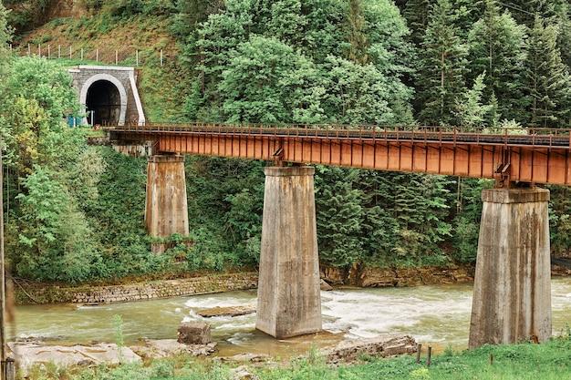 O velho trilho do trem acima do rio da montanha levando ao túnel
