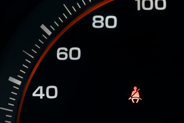 O velocímetro do carro com o painel de instrumentos aperta o sinal do cinto de segurança.