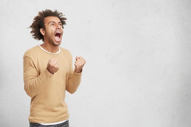 O vencedor africano grita de empolgação, fecha os punhos, alegra-se com seu sucesso e triunfo