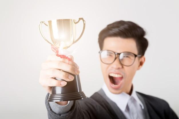 O vencedor segurando o troféu de ouro. o estúdio disparou no fundo branco.