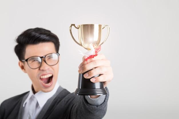 O vencedor segurando o troféu de ouro