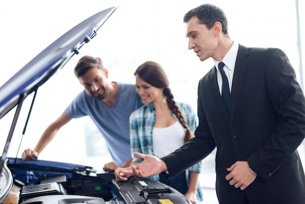 O vendedor ajuda a família jovem a escolher o carro.