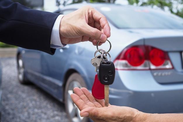 O vendedor de carros e a chave do novo proprietário.