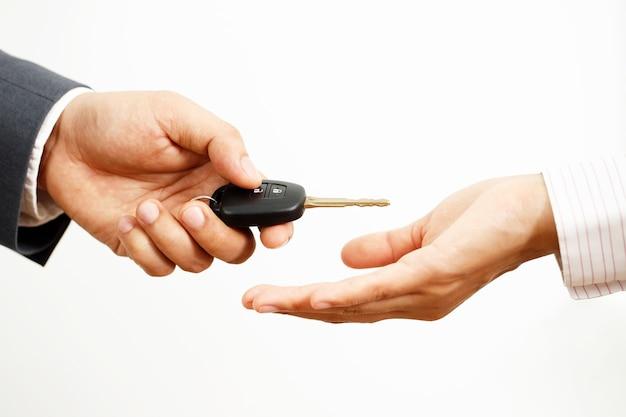 O vendedor de carros está entregando as chaves do carro aos clientes no showroom.