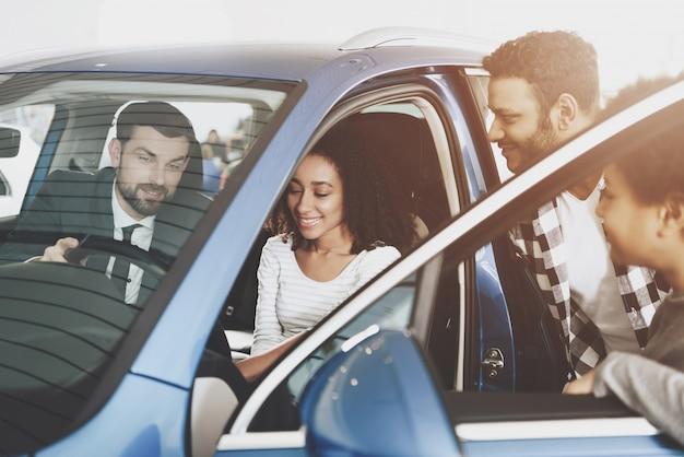 O vendedor demonstra o interior do carro à família afro.