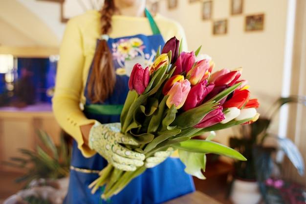 O vendedor detém um grande buquê lindo de tulipas embaladas. lado wiev