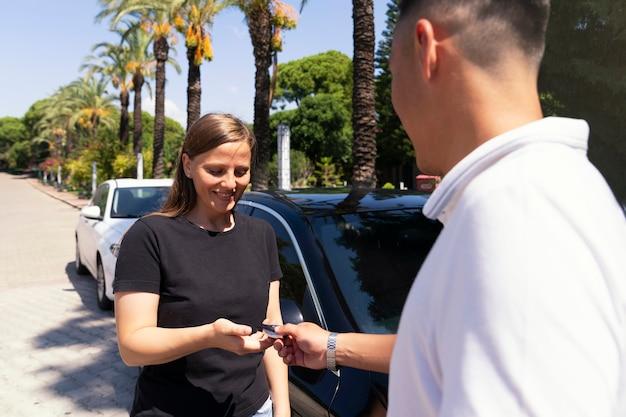 O vendedor do carro, um homem asiático, entrega a chave do carro para a nova proprietária, uma jovem de camiseta preta. alugar um carro ou um presente de um namorado.