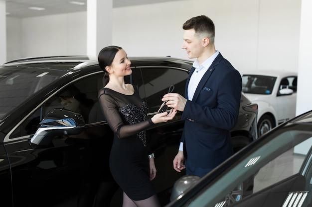 O vendedor entrega ao comprador as chaves de um carro novo no showroom