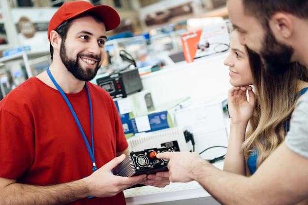 O vendedor está mostrando a ferramenta elétrica aos clientes