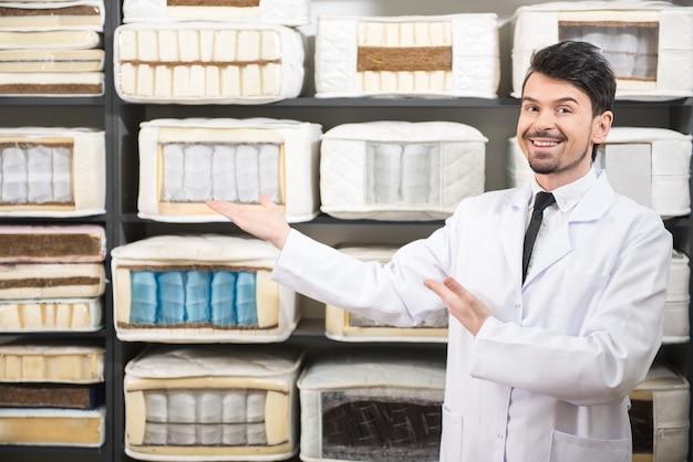 O vendedor está mostrando colchões de qualidade na loja.