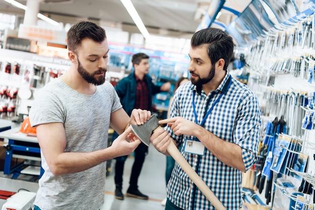 O vendedor está mostrando o machado novo ao cliente na loja.