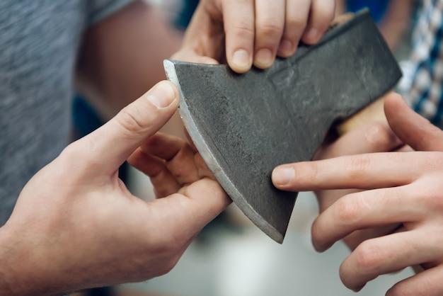 O vendedor fornece o cliente com que machado afiado da lâmina.