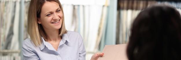 O vendedor mostra ao cliente as amostras de tecido no conceito de serviço ao cliente de catálogo