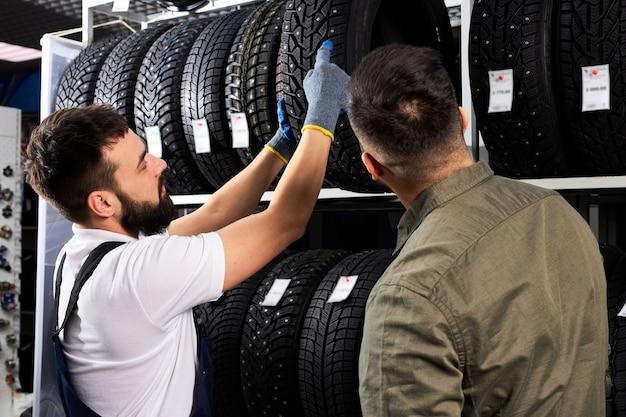O vendedor oferece novas rodas de borracha, pneus, aros para o carro. cliente do sexo masculino veio fazer compra em oficina mecânica. mecânico de automóveis mostrando variedade de pneus