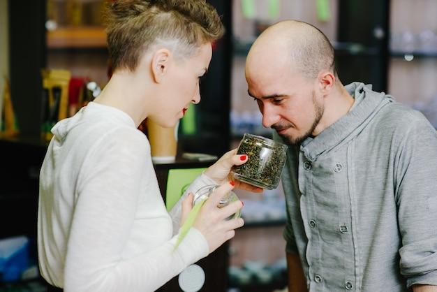 O vendedor oferece para cheirar chá ao cliente