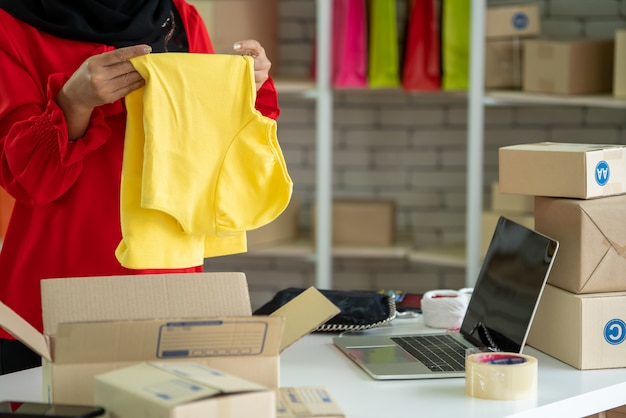 O vendedor on-line trabalha no escritório em casa e embala a caixa de entrega para o cliente.