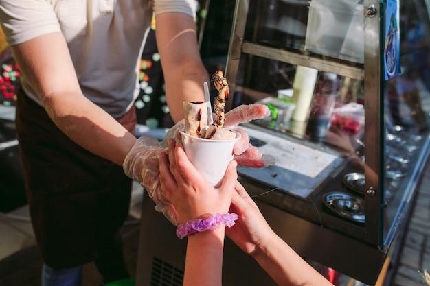 O vendedor passa o sorvete para uma garotinha. rolos de sorvete frito na panela de congelamento. orgânico, sorvete natural, sobremesa feita à mão.