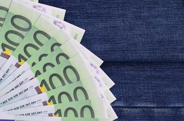 O ventilador de um monte de notas de euro está em uma superfície denim escuro