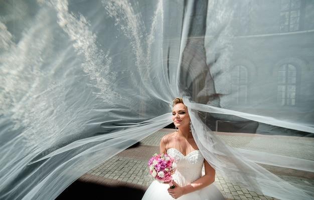 O vento sopra o véu da noiva em torno de seu belo rosto pensativo