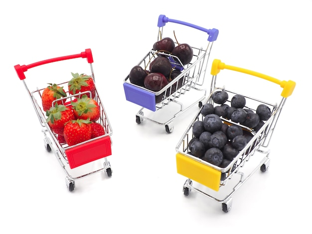 O verão fresco frutifica no carrinho de compras ou no trole isolados no fundo branco.
