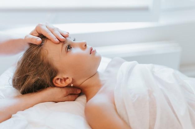 O verdadeiro médico osteopata faz terapia fisiológica e emocional para uma menina de oito anos. sessão de tratamento de osteopatia pediátrica. medicina alternativa. cuidando da saúde da criança