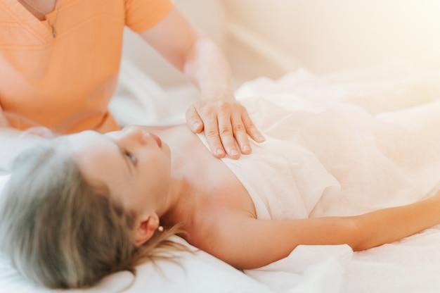 O verdadeiro médico osteopata faz terapia fisiológica e emocional para uma menina de oito anos. sessão de tratamento de osteopatia pediátrica. medicina alternativa. cuidar da saúde da criança. clarão