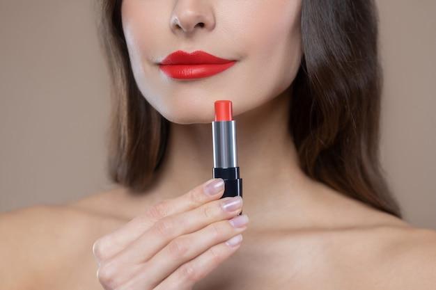 O vermelho é tendência. parte inferior do rosto da mulher e batom vermelho brilhante nos lábios bonitos e na mão