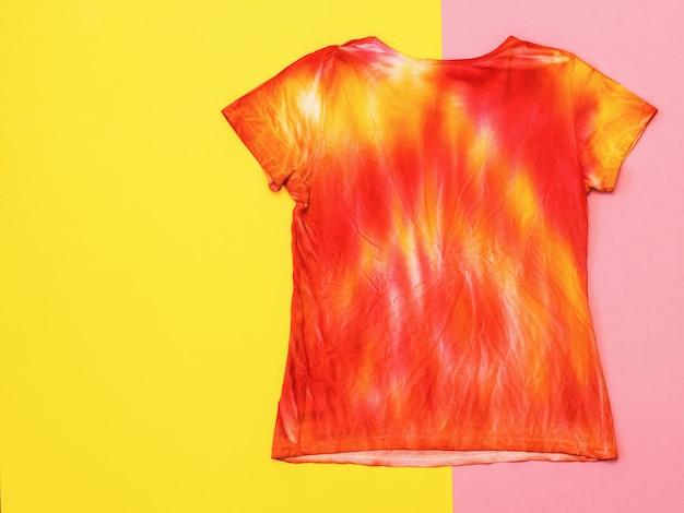 O verso da camiseta em estilo tie dye em um fundo amarelo e rosa