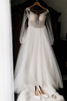 O vestido da noiva está pendurado e os sapatos da noiva em primeiro plano estão em um puf de pêlo