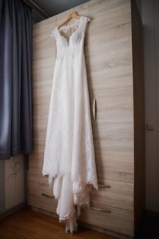 O vestido da noiva fica pendurado no guarda-roupa pela manhã