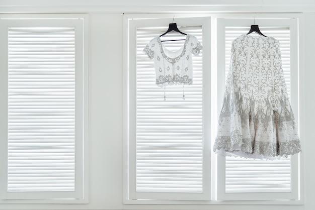 O vestido de casamento indiano, saree e blusa pendurada nas janelas brancas
