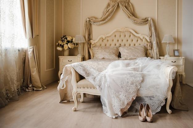 O vestido de noiva está no quarto da cama. sapatos de casamento bege.