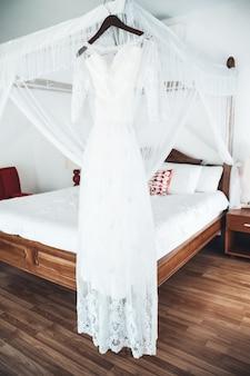 O vestido de noiva retrô perfeito com uma saia cheia em um cabide no quarto da noiva