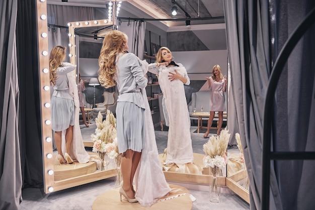 O vestido é incrível! comprimento total de mulheres jovens e atraentes experimentando um vestido de noiva enquanto passam um tempo na loja de noivas com a namorada