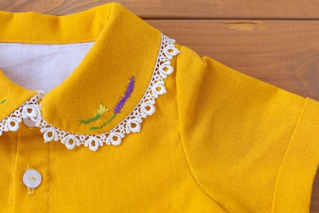 O vestido infantil é laranja com flores bordadas na gola. vestido de festa infantil.
