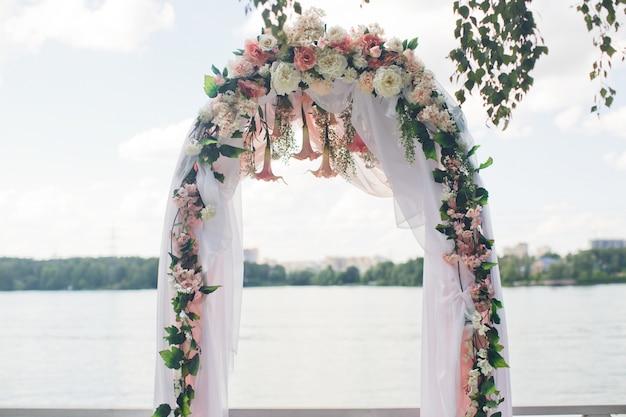 O véu paira no altar do casamento decorado com rosa e branco
