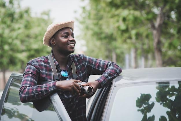 O viajante africano segurando uma câmera e parado com o carro